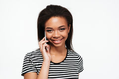 Cheerful young african lady talking by phone. Image of cheerful young african lady standing isolated over white background. Looking at camera while talking by Stock Photo