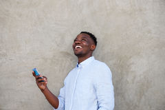 Cheerful young african man with mobile phone standing by wall Royalty Free Stock Photos