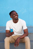 Cheerful young african man sitting on steps holding mobile phone Stock Photography