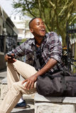 Cheerful young african man sitting by the street Royalty Free Stock Images
