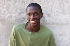 Cheerful young african man standing against wall. Close up portrait of cheerful young african man standing against wall Stock Photo