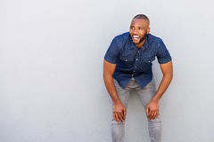 Cheerful young african man standing by wall with hands on knees. Portrait of cheerful young african man standing by wall with hands on knees stock image