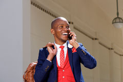 Cheerful young african man in suit talking on mobile phone Royalty Free Stock Photography