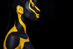 Cheerful young african woman with art fashion makeup. An amazing woman with black and yellow makeup royalty free stock photo