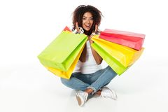 Cheerful young african woman holding shopping bags. Royalty Free Stock Photos