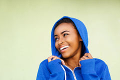 Cheerful young african woman laughing against green wall Stock Photo