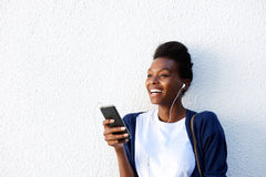 Cheerful young african woman listening music on smart phone Stock Photo