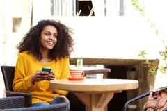 Cheerful young african woman sitting at outdoor cafe Royalty Free Stock Photography