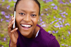 Cheerful young african woman talking on cell phone Stock Photos