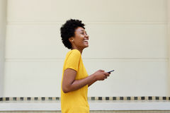 Cheerful young african woman walking with a mobile phone Royalty Free Stock Photos