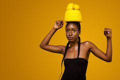 Cheerful young african woman with yellow makeup on her eyes. Female model against yellow background with yellow lemons. stock image