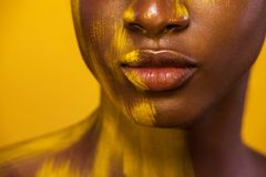 Closeup lips portrait. Cheerful young african woman with yellow makeup. Female model against yellow background. stock photo