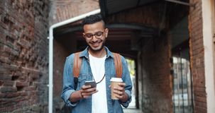 Cheerful young Arab touching smartphone screen holding coffee cup outdoors. In the street smiling looking at device. Modern technology and happy youth concept stock footage