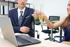 Cheerful young Asian business partners clinking bottle of wine in office. Successful and celebration concept. Stock Photos
