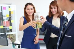 Cheerful young Asian business partners clinking bottle of wine in office. Successful and celebration concept royalty free stock photo
