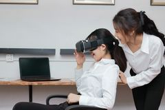 Cheerful young Asian business woman wearing virtual VR reality glasses and having fun in office. Cheerful young Asian business women wearing virtual VR reality Royalty Free Stock Images