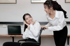 Cheerful young Asian business woman push chair and having fun together in office. Cheerful young Asian business women push chair and having fun together in Stock Photography
