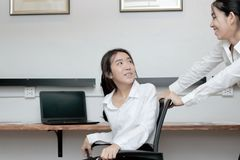 Cheerful young Asian business woman push chair and having fun together in office. Cheerful young Asian business women push chair and having fun together in Stock Photos
