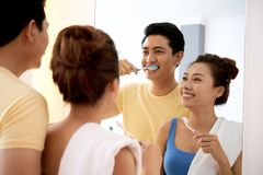 Couple brushing teeth. Cheerful young Asian couple looking at mirror and brushing teeth together stock images