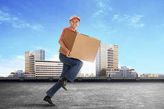 Cheerful Young Asian Courier Holding A Cardboard Box Stock Images