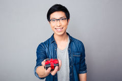 Cheerful young asian man with gift box Stock Photo