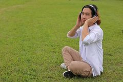Cheerful young asian man listening to music with headphone in green grass with copy space background. royalty free stock photo