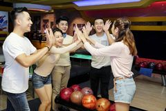 Friends celebrating victory with in bowling center. Cheerful young Asian people giving each other high five after winning game in bowling club stock photo