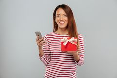 Cheerful young asian woman chatting by phone holding gift. Image of cheerful young asian woman chatting by phone standing isolated over grey wall. Looking Stock Image