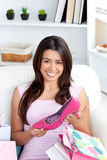 Cheerful young asian woman holding a shoe on sofa Royalty Free Stock Photo