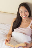 Cheerful young asian woman sitting in bed reading a book looking Stock Photos