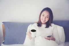 Cheerful young asian woman sitting in bed with smartphone and drinking coffee. Stock Image