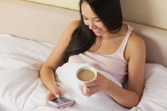 Cheerful young asian woman sitting in bed texting on her smartph Royalty Free Stock Photos