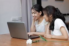 Cheerful young Asian woman using laptop computer for shopping online in living room. Cheerful young Asian women using laptop computer for shopping online in Royalty Free Stock Image