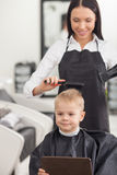 Cheerful young barber is using dryer in Royalty Free Stock Images