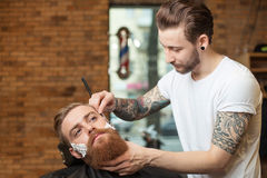 Cheerful young barber is working with shaver Stock Photos