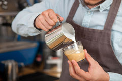 Cheerful young barista is brewing coffee in cafe Stock Photo