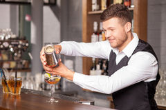 Cheerful young barman is making cocktail in bar Stock Photography