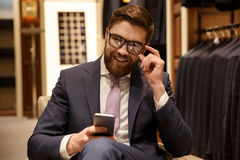 Cheerful young bearded businessman chatting by phone. Royalty Free Stock Photography