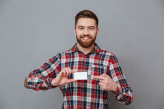 Cheerful young bearded man with copyspace business card Royalty Free Stock Photos