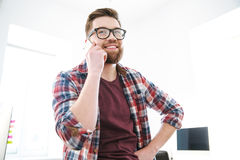 Cheerful young bearded man in glasses talking on mobile phone. In the office and smiling Stock Photography