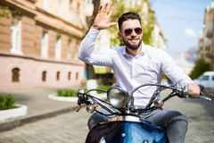 Cheerful young bearded man in helmet is sitting on scooter and say hello on city street Stock Image