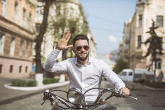 Cheerful young bearded man in helmet is sitting on scooter and say hello on city street. toned. Royalty Free Stock Image
