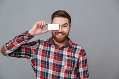 Cheerful young bearded man holding copyspace business card. Photo of cheerful young bearded man holding copyspace business card standing over grey background Royalty Free Stock Image
