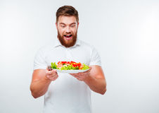 Cheerful young bearded man holding plate with fresh salad Stock Photography