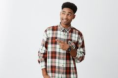 Cheerful young beautiful black man with afro hairstyle in stylish casual shirt smiling with teeth, pointing on free Stock Photo