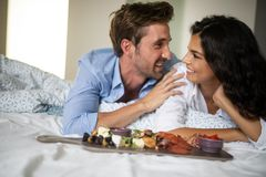 Cheerful young couple having breakfast in bed stock photos