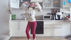 Cheerful young beautiful woman is dancing in kitchen wearing pajamas and headphones in the morning listening to music on stock video