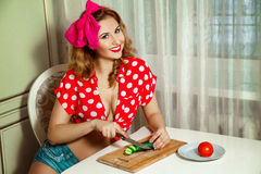 Cheerful young beautiful woman sliced cucumber on the kitchen an Royalty Free Stock Photos
