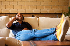 Cheerful young black man lying on sofa with headphones and listening to music Royalty Free Stock Images