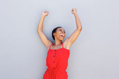 Cheerful young black woman with arms raised Royalty Free Stock Photos